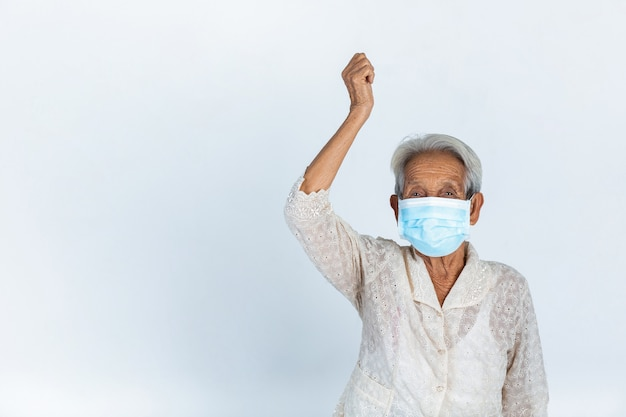 Grandmother is putting her hand up  in air on white back ground - concept mask campaign Free Photo