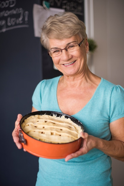 Grandmother proud of her homemade cake Free Photo