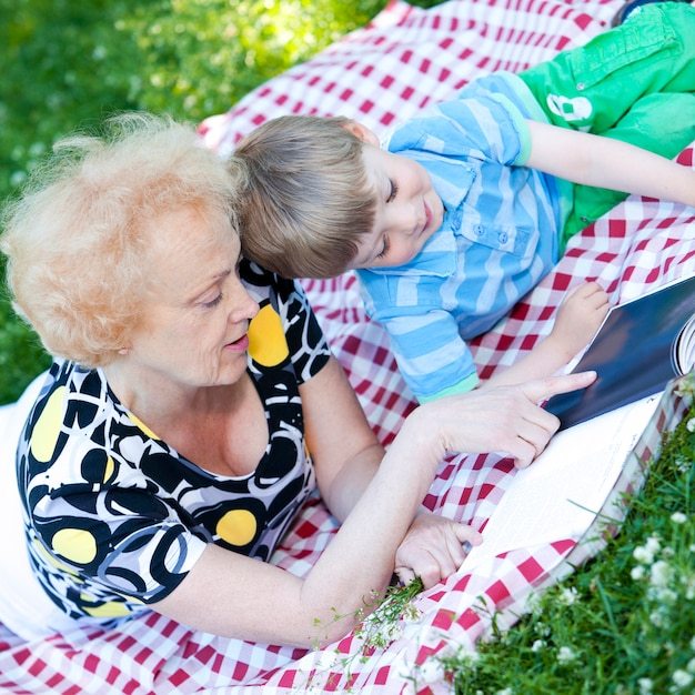 Grandmother reading book to her grandson Free Photo
