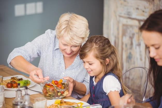 Grandmother serving granddaughter while having breakfast Premium Photo