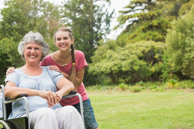 Grandmother in wheelchair and granddaughter smiling into the camera Premium Photo