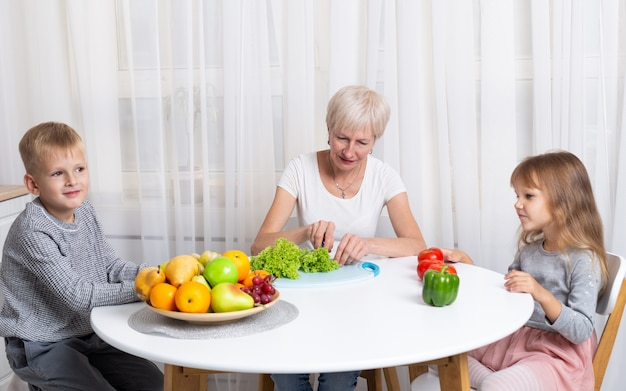Grandmother with grandson and granddaughter prepare healthy food in the kitchen. family preparing a salad together Premium Photo