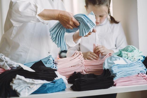 小さな孫娘と祖母が裁縫用の生地を測定します 無料写真