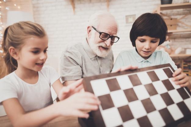 Grandpa and children open chess board at home Premium Photo