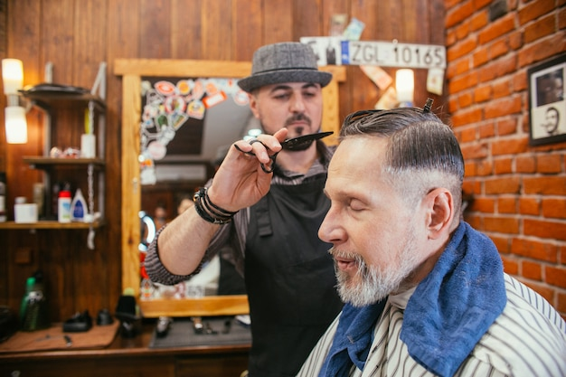 Grandpa gets a haircut at the hairdresser in barber shop. trendy haircut of an old man Premium Photo