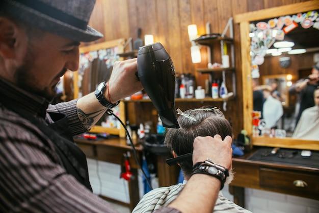 Grandpa gets a haircut at the hairdresser in barber shop. trendy haircut Premium Photo
