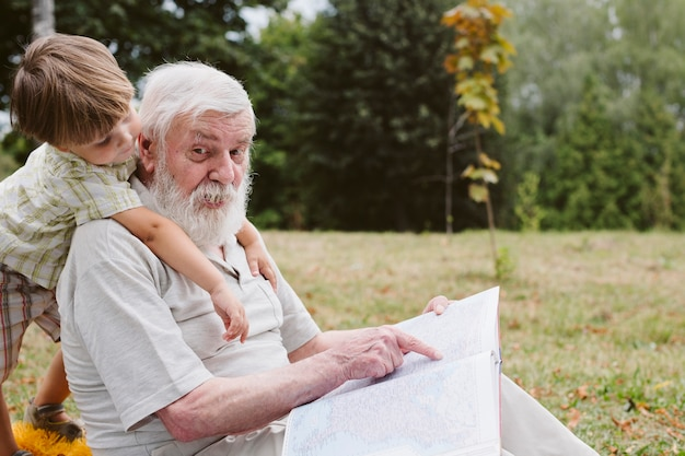 Grandpa and grandson in park story time Free Photo