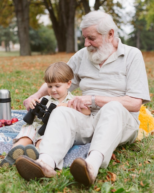 Grandpa showing binocular to grandson Free Photo
