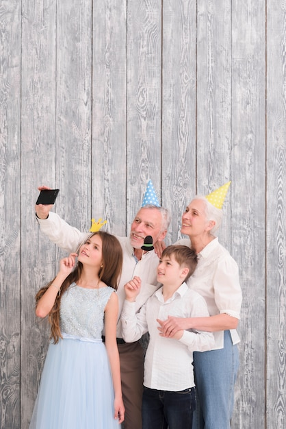 Grandparent wearing party hat taking selfie on mobile phone with their grandchildren holding paper props Free Photo