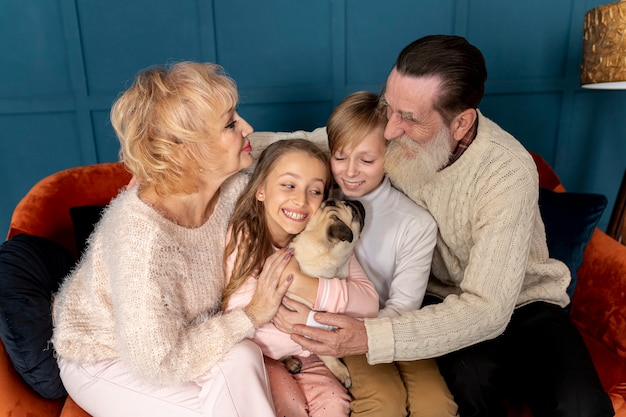 Grandparents and grandchildren playing with dog together Free Photo