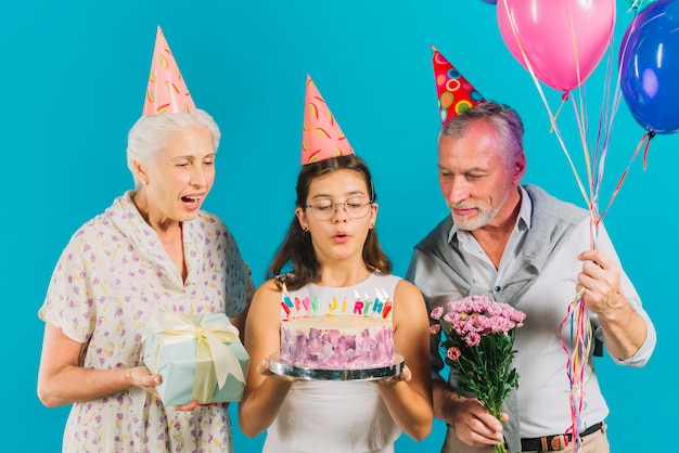 Grandparents holding birthday gifts near girl with cake blowing candles on blue backdrop Free Photo