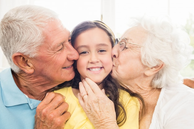Grandparents kissing their granddaughter at home Premium Photo