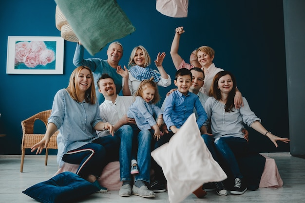 Grandparents, parents and their little children sit together on the bed in a blue room Free Photo