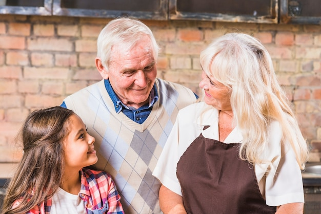 Grandparents with granddaughter in kitchen Free Photo