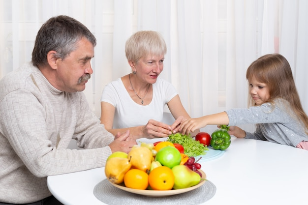 Grandparents with granddaughter prepare healthy food in the kitchen. family preparing a salad together Premium Photo