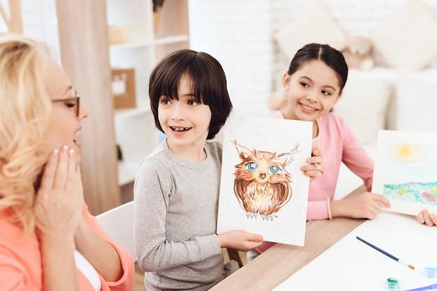 Grandson showing picture grandma drawing concept Premium Photo
