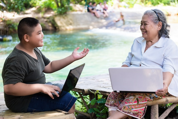 Grandson teaching his elderly female use laptop Free Photo