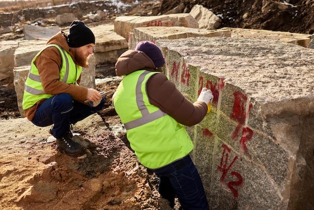 Granitブロックをマークする2人の労働者 Premium写真