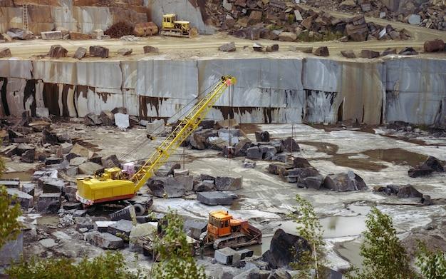 Гранитный рудник с экскаваторами тяжелого оборудования, загружающими необработанные породы Premium Фотографии