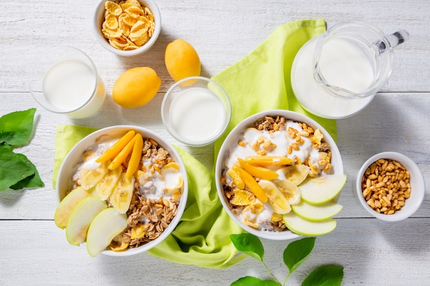 Гранола и вегетарианский йогурт с кусочками яблока, абрикоса, банана и кувшин молока на белой деревянной поверхности. концепция здорового завтрака. вид сверху Premium Фотографии