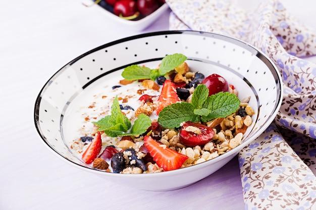 Granola, strawberries, cherry, honeysuckle berry, nuts and yogurt in a bowl Free Photo