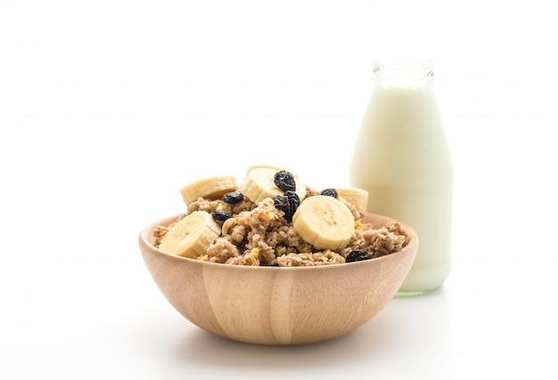 Granola with banana, raisin and milk for breakfast Premium Photo