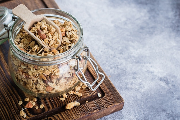 Granola with nut mix in jar on wooden board on stone table background Premium Photo