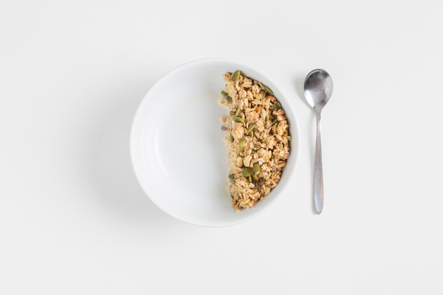 Granola with pumpkin seeds in white bowl and spoon on white background Free Photo