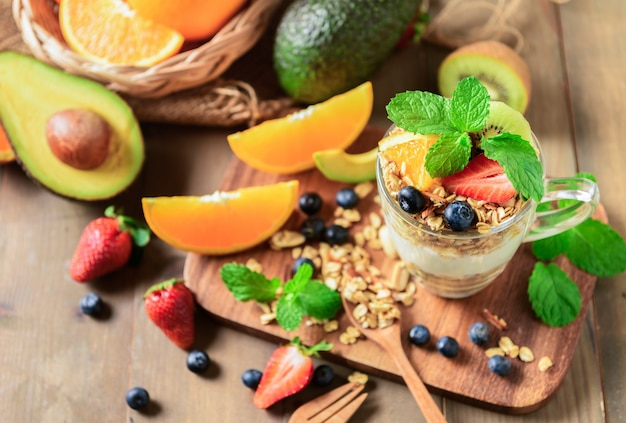 Granola and yogurt and fruits on topping in glass Premium Photo