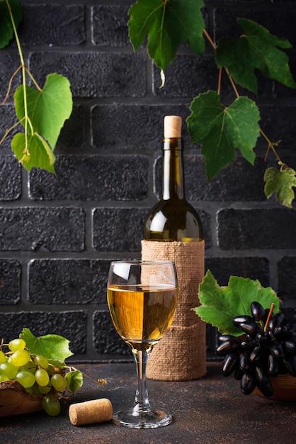 Grape, bottle and glass of white wine Premium Photo