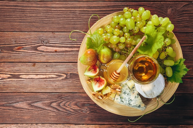 Grape, cheese, figs and honey with wine on wooden table Premium Photo