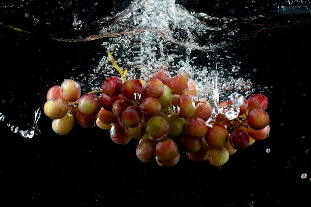 Grape cluster splashed into water in black Free Photo