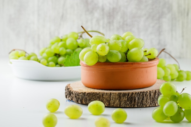 Grape clusters with wooden piece in plates on white surface Free Photo
