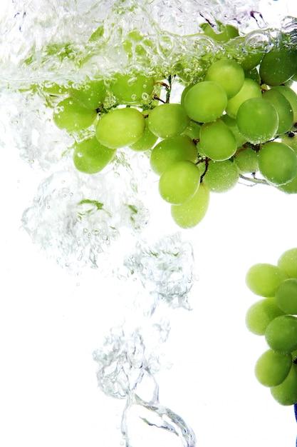 Grape dropped into water Free Photo