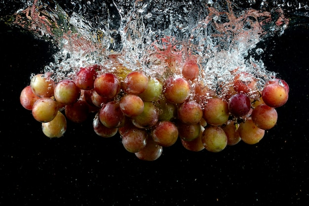 Grape splashed into water in the black Free Photo
