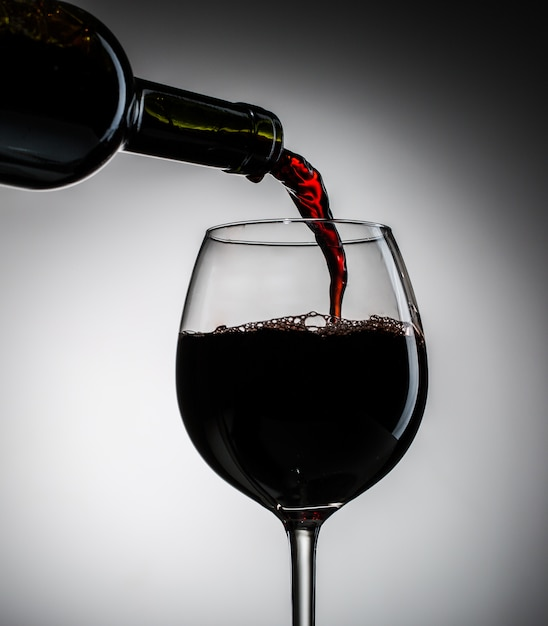 Grape wine poured from bottle into wine glass from glass Premium Photo
