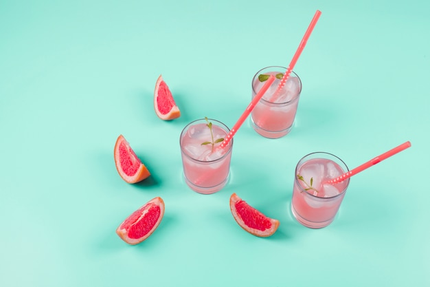 Grapefruit citrus fruit slices and cold juice on mint background Free Photo