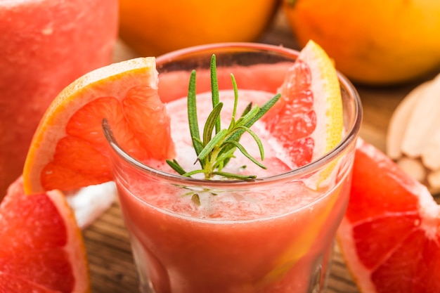 ローズマリーとテーブルの上のグラスに氷とグレープフルーツジュース。 Premium写真