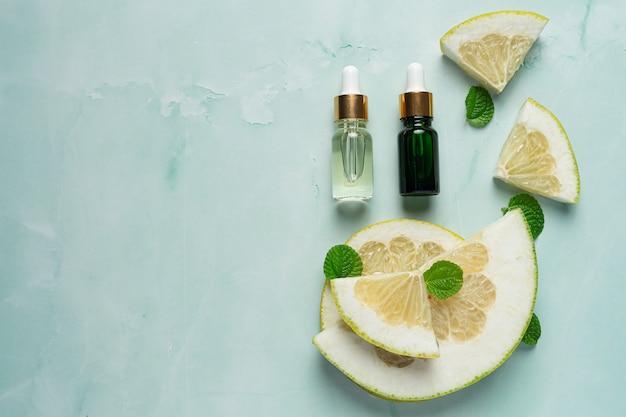 Bottiglia di siero olio di pompelmo messa su sfondo verde chiaro Foto Gratuite