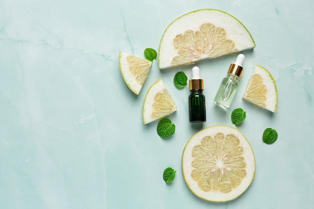 Бутылка сыворотки с маслом грейпфрута на фоне зеленого света Бесплатные Фотографии