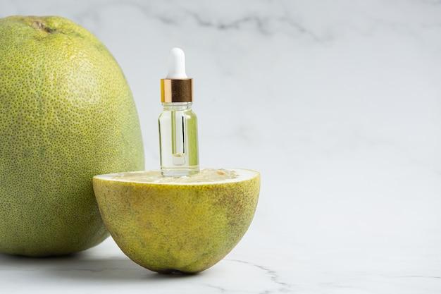Бутылка сыворотки с маслом грейпфрута на белом мраморном фоне Бесплатные Фотографии