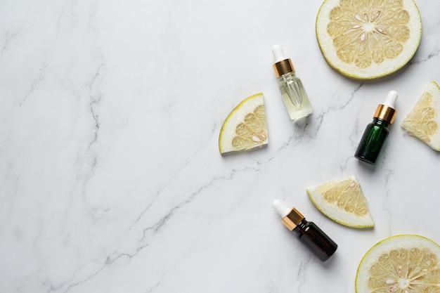 Grapefruit oil serum bottle put on white marble background Free Photo