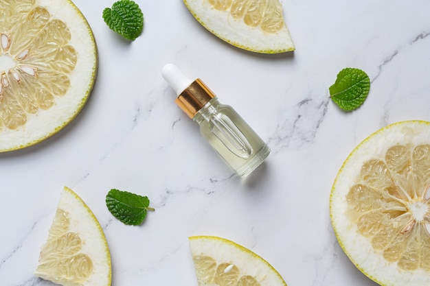 Bottiglia di siero olio di pompelmo messa su sfondo bianco marmo Foto Gratuite