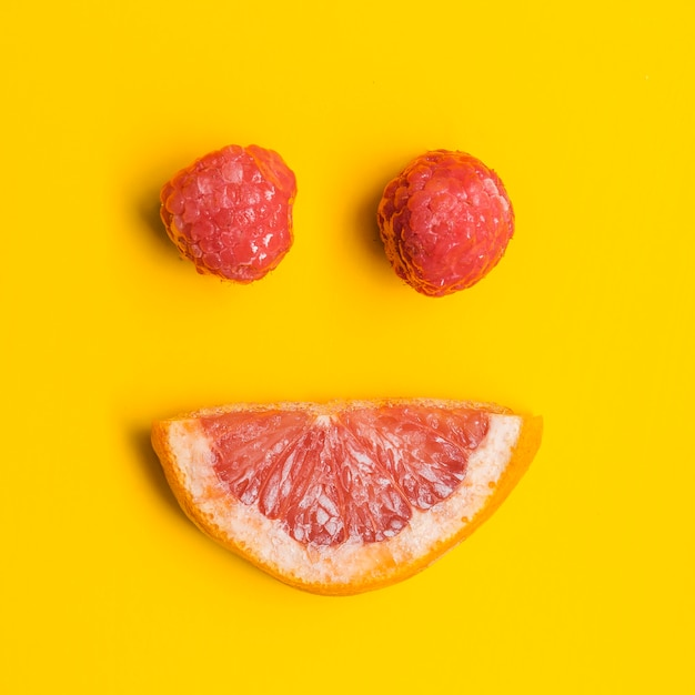 Grapefruit and raspberries in form of smile Free Photo