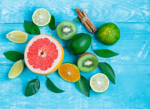 Ломтики грейпфрута, киви, лайм, листья и палочки корицы Бесплатные Фотографии