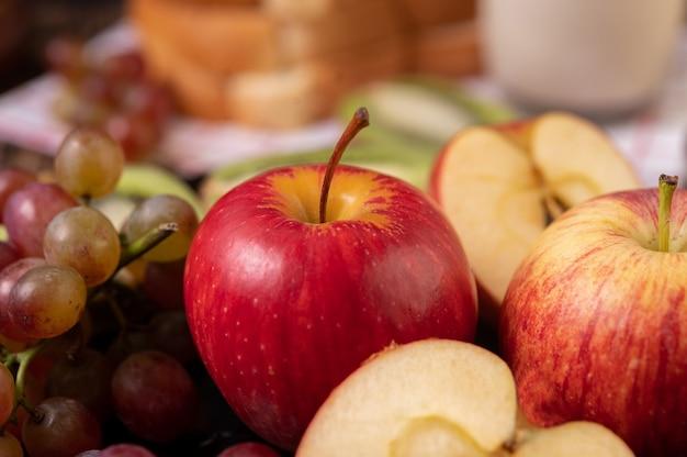 Uva, mele e pane in un piatto sul tavolo Foto Gratuite