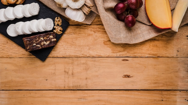 Grapes; garlic and variety of cheeses on jute textile over wooden plank Free Photo