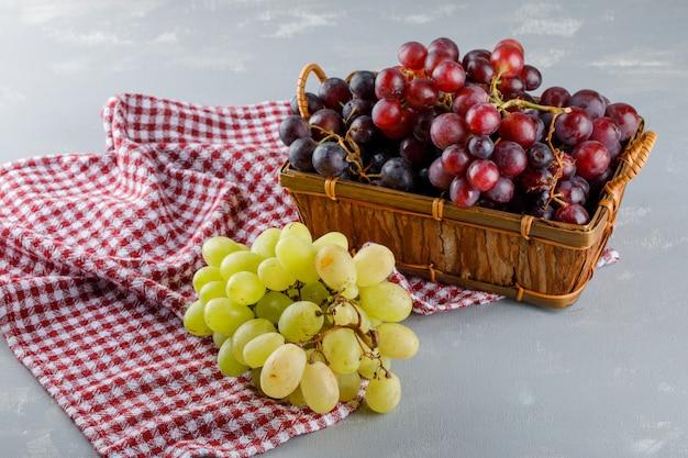 Виноград в корзине на ткани для пикника и гипсе. высокий угол обзора. Бесплатные Фотографии