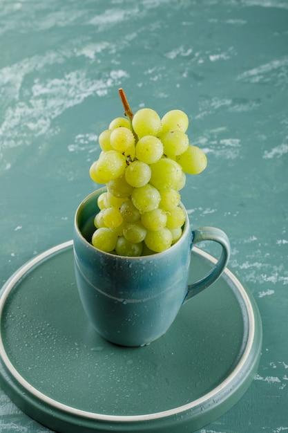石膏とトレイの背景にカップの高角度のビューのブドウ 無料写真