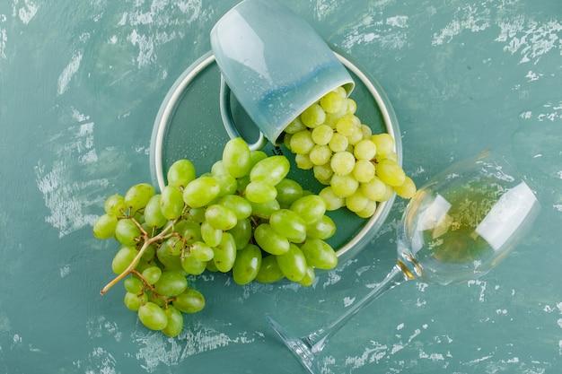 フラットドリンクカップのブドウは石膏とトレイの背景に置く 無料写真